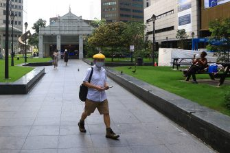 SINGAPORE - MAY 26:  A man wearing face shield mask and a protective mask walks at an unusually quiet Raffles Place central business district on May 26, 2020 in Singapore. Singapore is set to ease the partial lockdown measures against the coronavirus (COVID-19) pandemic after 1 June in three phases to resume activities safely after it sees a decline in the new infection cases in the community. Singapore's gross domestic product (GDP) is expected to shrink as much as 7 percent this year as the country battles the slump in global trade and travel amid the coronavirus pandemic, according to the government report in the local media today.  (Photo by Suhaimi Abdullah/Getty Images)