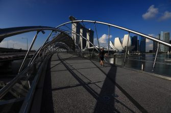 SINGAPORE - MAY 26:  A man wearing protective mask walks along the Helix Bridge with the Marina Bay Sands, ArtScience Museum and the central business district pictured in the background on May 26, 2020 in Singapore. Singapore is set to ease the partial lockdown measures against the coronavirus (COVID-19) pandemic after 1 June in three phases to resume activities safely after it sees a decline in the new infection cases in the community. Singapore's gross domestic product (GDP) is expected to shrink as much as 7 percent this year as the country battles the slump in global trade and travel amid the coronavirus pandemic, according to the government report in the local media today.  (Photo by Suhaimi Abdullah/Getty Images)