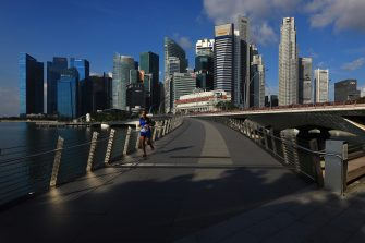 SINGAPORE - MAY 26:  A man jogs along the Jubilee Bridge with the central business district pictured in the background on May 26, 2020 in Singapore. Singapore is set to ease the partial lockdown measures against the coronavirus (COVID-19) pandemic after 1 June in three phases to resume activities safely after it sees a decline in the new infection cases in the community. Singapore's gross domestic product (GDP) is expected to shrink as much as 7 percent this year as the country battles the slump in global trade and travel amid the coronavirus pandemic, according to the government report in the local media today.  (Photo by Suhaimi Abdullah/Getty Images)