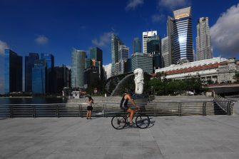 SINGAPORE - MAY 26:  People are seen at Merlion Park with the central business district pictured in the background on May 26, 2020 in Singapore. Singapore is set to ease the partial lockdown measures against the coronavirus (COVID-19) pandemic after 1 June in three phases to resume activities safely after it sees a decline in the new infection cases in the community. Singapore's gross domestic product (GDP) is expected to shrink as much as 7 percent this year as the country battles the slump in global trade and travel amid the coronavirus pandemic, according to the government report in the local media today.  (Photo by Suhaimi Abdullah/Getty Images)