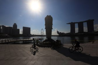 SINGAPORE - MAY 26:  People cycle past a cordoned off Merlion Park on May 26, 2020 in Singapore. Singapore is set to ease the partial lockdown measures against the coronavirus (COVID-19) pandemic after 1 June in three phases to resume activities safely after it sees a decline in the new infection cases in the community. Singapore's gross domestic product (GDP) is expected to shrink as much as 7 percent this year as the country battles the slump in global trade and travel amid the coronavirus pandemic, according to the government report in the local media today.  (Photo by Suhaimi Abdullah/Getty Images)