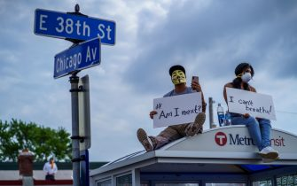 People hold signs and sit on a bus stop during a protest near where a Minneapolis Police Department officer allegedly killed George Floyd, on May 26, 2020 in Minneapolis, Minnesota. - A video of a handcuffed black man dying while a Minneapolis officer knelt on his neck for more than five minutes sparked a fresh furor in the US over police treatment of African Americans Tuesday. Minneapolis Mayor Jacob Frey fired four police officers following the death in custody of George Floyd on Monday as the suspect was pressed shirtless onto a Minneapolis street, one officer's knee on his neck. (Photo by kerem yucel / AFP) (Photo by KEREM YUCEL/AFP via Getty Images)