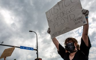 A woman holds up a sign during a protest near where a Minneapolis Police Department officer allegedly killed George Floyd, on May 26, 2020 in Minneapolis, Minnesota. - A video of a handcuffed black man dying while a Minneapolis officer knelt on his neck for more than five minutes sparked a fresh furor in the US over police treatment of African Americans Tuesday. Minneapolis Mayor Jacob Frey fired four police officers following the death in custody of George Floyd on Monday as the suspect was pressed shirtless onto a Minneapolis street, one officer's knee on his neck. (Photo by Kerem Yucel / AFP) (Photo by KEREM YUCEL/AFP via Getty Images)