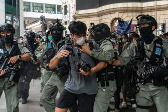HONG KONG, CHINA - MAY 27: A pedestrian is detained by riot police during a Lunch with You rally in Central district on May 27, 2020 in Hong Kong, China. Chinese Premier Li Keqiang said on Friday during the National People's Congress that Beijing would establish a sound legal system and enforcement mechanism for safeguarding national security in Hong Kong.(Photo by Anthony Kwan/Getty Images)