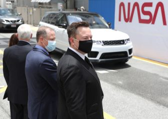 CAPE CANAVERAL, FLORIDA - MAY 27: SpaceX founder Elon Musk (L) wears a face mask as he watches NASA astronauts Bob Behnken and Doug Hurley depart from the Operations and Checkout Building on their way to the SpaceX Falcon 9 rocket with the Crew Dragon spacecraft on launch pad 39A at the Kennedy Space Center on May 27, 2020 in Cape Canaveral, Florida. The inaugural flight will be the first manned mission since the end of the Space Shuttle program in 2011 to be launched into space from the United States.  (Photo by Joe Raedle/Getty Images)