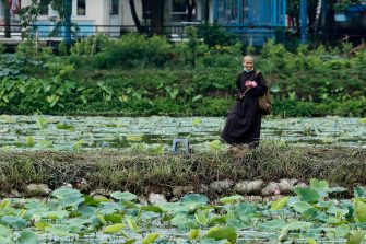 epa08446322 A nun holding lotus flowers walks by a lake in Hanoi, Vietnam, 27 May 2020. Traditions sees for Vietnamese people use the inner parts of the lotus to mix with tea in oder to get a unique fragrance. Lotus flower season is usually from late May through to August.  EPA/LUONG THAI LINH