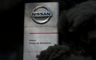 The logo of Nissan is covered by smoke columns as employees burn tyres in front of the Japanese cars manufacturer's plant in Barcelona on May 28, 2020, to they protest against the factory closure. - Japanese carmaker Nissan has decided to shut its factory in Barcelona where 3,000 people are employed, the Spanish government said today. (Photo by LLUIS GENE / AFP) (Photo by LLUIS GENE/AFP via Getty Images)