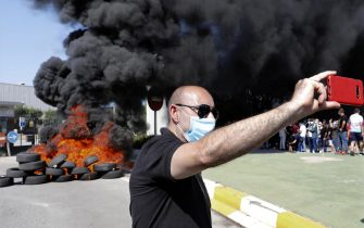 epa08449357 A man takes a selfie as Nissan workers burn tires outside the Nissan's plant at Zona Franca industrial state after the company announced its plans of shutting down the plant in Barcelona, Spain, 28 May 2020. Japanese carmaker Nissan reported that it will dismantle Barcelona's facilities affecting up to 30,000 direct and indirect jobs after some 40 years of business.  EPA/Andreu Dalmau