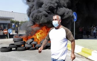 epa08449358 A man walks past a burnt barricade during a protest held outside the Nissan's plant at Zona Franca industrial state after the company announced its plans of shutting down the plant in Barcelona, Spain, 28 May 2020. Japanese carmaker Nissan reported that it will dismantle Barcelona's facilities affecting up to 30,000 direct and indirect jobs after some 40 years of business.  EPA/Andreu Dalmau