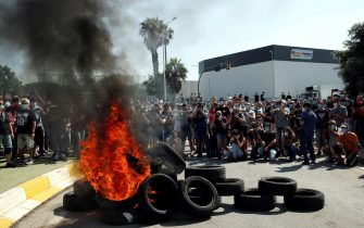epa08449137 Several photographers using their cameras stand behind burning tires as Nissan workers protest outside Nissan's plant at Zona Franca industrial state after the Japanese company announced its plans of shutting down the plant in Barcelona, northeastern Spain, 28 May 2020. Nissan reported that it will dismantle Barcelona's facilities affecting up to 30,000 direct and indirect jobs after some 40 years of business.  EPA/ALEJANDRO GARCIA