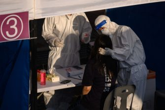 A health worker administers a swab at a temporary COVID-19 novel coronavirus testing centre in Bucheon, south of Seoul, on May 27, 2020. - South Korea reported its biggest jump in coronavirus infections in seven weeks on May 27, driven by a fresh cluster at an e-commerce warehouse on Seoul's outskirts, as millions more pupils went back to school. (Photo by Ed JONES / AFP) (Photo by ED JONES/AFP via Getty Images)