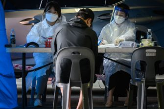 Health workers recieve visitors to a temporary COVID-19 novel coronavirus testing centre in Bucheon, south of Seoul, on May 27, 2020. - South Korea reported its biggest jump in coronavirus infections in seven weeks on May 27, driven by a fresh cluster at an e-commerce warehouse on Seoul's outskirts, as millions more pupils went back to school. (Photo by Ed JONES / AFP) (Photo by ED JONES/AFP via Getty Images)