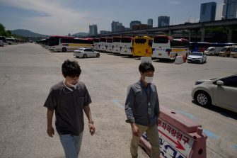 Two men wearing face masks walk before tour busses stored in a parking lot in Seoul amid a downturn in tourism due to the covid-19 novel coronavirus pandemic, on May 27, 2020. (Photo by Ed JONES / AFP) (Photo by ED JONES/AFP via Getty Images)