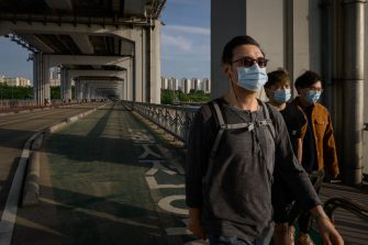 In a photo taken on May 24, 2020 people wearing face masks amid concerns of the COVID-19 novel coronavirus walk along a bridge across the Han river in Seoul. (Photo by Ed JONES / AFP) (Photo by ED JONES/AFP via Getty Images)
