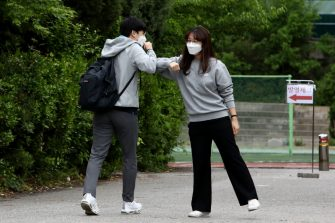 SEOUL, SOUTH KOREA - MAY 20: A teacher (R) welcomes a student back to school at Kyungbock high school on May 20, 2020 in Seoul, South Korea. Senior high school students are able to return to school from today, as South Koreans take measures to protect themselves against the spread of coronavirus (COVID-19). South Korea's education ministry announced plans to re-open schools starting for senior high school students, more than two months after schools were closed in a precautionary measure against the coronavirus. (Photo by Chung Sung-Jun/Getty Images)