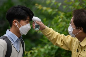 Students wearing facemasks amid concerns over the COVID-19 novel coronavirus undergo a temperature check from city education officials as they arrive at Kyungbock High School in Seoul on May 20, 2020. - Hundreds of thousands of South Korean students returned to classes as schools started reopening after more than a two-month delay over the coronavirus outbreak. (Photo by Ed JONES / AFP) (Photo by ED JONES/AFP via Getty Images)