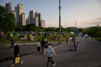 In a photo taken on May 24, 2020 people wearing face masks amid concerns of the COVID-19 novel coronavirus walk through a park in Seoul. (Photo by Ed JONES / AFP) (Photo by ED JONES/AFP via Getty Images)