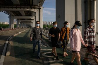 In a photo taken on May 24, 2020, people wearing face masks amid concerns of the COVID-19 novel coronavirus walk along a bridge across the Han river in Seoul. (Photo by Ed JONES / AFP) (Photo by ED JONES/AFP via Getty Images)