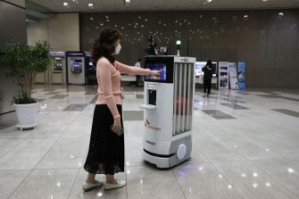 SEOUL, SOUTH KOREA - MAY 26: An employee of SK Telecom demonstrates a robot that will be used for disinfection, checking body temperature at their company headquarters on May 26, 2020 in Seoul, South Korea. SK Telecom has developed a new autonomous robot to handle disinfection and monitoring duties as part of efforts to prevent the spread of coronavirus (COVID-19), the company said. It will also monitor the temperatures of people around it and check whether they are wearing face masks. Those who are not wearing masks will be asked to do so by the robot if there are too many people around. They said it hopes the robots will lessen the workloads of people who are performing monitoring duties amid the COVID-19 pandemic. (Photo by Chung Sung-Jun/Getty Images)