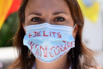 A protester wearing a protective facemask takes part in a demonstration of health workers in front of La Timone hospital in Marseille, southern France, on May 26, 2020, to call for a pay rise within the health sector as the government has launched general talks on Health amid the crisis caused by the Covid-19 pandemic (novel coronavirus). (Photo by Christophe SIMON / AFP) (Photo by CHRISTOPHE SIMON/AFP via Getty Images)