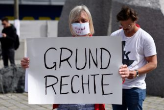 "VIENNA, AUSTRIA - APRIL 24: A participant with a face mask reading ""silenced"" and a sign reading ""fundamental rights"" poses during a demonstration against the government measures to slow down the spread of coronvirus on April 24, 2020 in Vienna, Austria. The demonstration was forbidden to avoid possible COVID-19 infections. (Photo by Thomas Kronsteiner/Getty Images)"