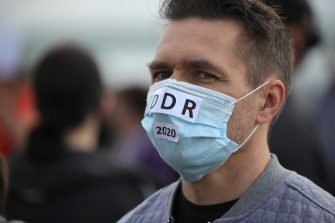 "COLOGNE, GERMANY - MAY 23: A protester, wearing a face mask with a sign that reads ""DDR 2020"" demonstrates against lockdown measures and government policy on the 71st anniversary of Germany's Basic Law during the coronavirus crisis on May 23, 2020 in Cologne, Germany. The protests, which include people from the far political left to the far right, from conspiracy theorists to anti-vaccinators, but also the simply disgruntled, have become a weekly event in cities across Germany despite the fact that authorities have eased most lockdown measures. (Photo by Andreas Rentz/Getty Images)"