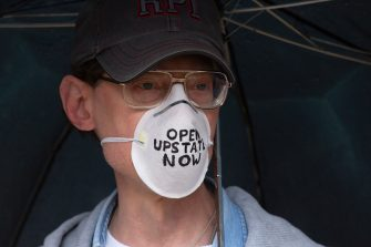 ALBANY, NY - MAY 01: A protestor wears a face mask calling for New York State to be reopened as demonstrators gather outside of the New York State Capitol Building on May 1, 2020 in Albany, New York.  New York State Governor Andrew Cuomo has stated that he will consider easing shut-down requirements in regions of the state beginning May 15th.  (Photo by Stefani Reynolds/Getty Images)