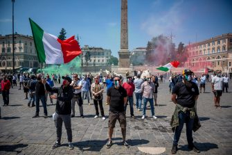 "ROME, ITALY - MAY 23: Supporters of the far-right political movement CasaPound, wearing protective masks with the Italian tricolor, take part in a demonstration to protest against the Italian government, during Italy's phase two coronavirus (Covid-19) lockdown exit plan, on May 23, 2020 in Rome, Italy. The protest demonstration against the Italian government was organized by the spontaneous Facebook group ""Mascherine Tricolori"" (Tricolor masks) to support Italian trade and businesses in serious difficulty due to the Covid pandemic. Churches, restaurants, bars, cafes, hairdressers and other shops have reopened, subject to social distancing measures, after more than two months of a nationwide lockdown meant to curb the spread of Covid-19. (Photo by Antonio Masiello/Getty Images)"