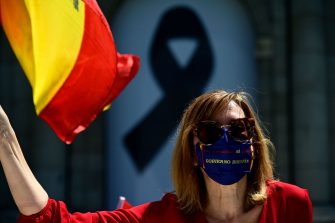 "A demonstrator wearing a mask calling for the resignation of the government waves a Spanish flag while driving past the Puerta de Alcala during a ""caravan for Spain and its freedom"" protest by far-right party Vox against the Spanish government in Madrid on May 23, 2020. - Spain, one of the most affected countries in the world by the novel coronavirus with 28,628 fatalities, has extended until June 6 the state of emergency which significantly limits the freedom of movement to fight the epidemic. The left-wing government's management of the crisis has drawn a barrage of criticism from righ-wing parties who have denounced its ""brutal confinement"". (Photo by JAVIER SORIANO / AFP) (Photo by JAVIER SORIANO/AFP via Getty Images)"