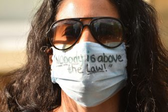 "A woman wears a face mask with a message written on it that reads ""nobody is above the law"" outside the home of Number 10 Downing Street special advisor Dominic Cummings in London on May 24, 2020 following allegations he broke coronavirus lockdown rules by travelling across the country in March. - British Prime Minister Boris Johnson on Sunday defied pressure from within his own party and backed top aide Dominic Cummings over allegations he breached coronavirus lockdown rules. (Photo by Glyn KIRK / AFP) (Photo by GLYN KIRK/AFP via Getty Images)"