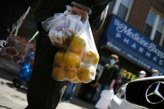 NEW YORK, NY - MAY 22: People receive food after waiting on line for hours outside of a Brooklyn mosque and cultural center on May 22 , 2020 in New York City. The center distributes food from local food banks and charities to anyone in need and usually sees up to 2000 people during a distribution, a number that continues to rise with New Yorker's needs.The number of people going hungry in the five boroughs has risen sharply during the COVID-19 pandemic and city officials have said that up to 2 million New Yorkers currently face food insecurity. (Photo by Spencer Platt/Getty Images)