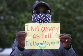 (FILES) In this file photo taken on May 22, 2020, Odirus Charles holds a sign that reads, ' I Am angry as hell Fix Unemployment Now,' as he joins others in a protest in Miami Beach, Florida. - Another 2.12 million people filed for unemployment in the US last week, pushing total layoffs since the start of the coronavirus crisis to more than 40 million, a level not seen since the Great Depression, the Labor Department said on May 28, 2020. The new filings, however, showed that the pace of the layoffs was subsiding as the US economy slowly begins to reopen. (Photo by JOE RAEDLE / GETTY IMAGES NORTH AMERICA / AFP)