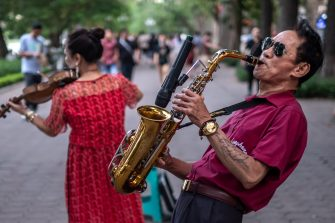 HANOI, VIETNAM - MAY 17: A saxophonist plays with his band on Hoan Kiem pedestrian street on May 17, 2020 in Hanoi, Vietnam. Though some restrictions remain in place, Vietnam has lifted the ban on certain entertainment facilities and non-essential businesses, including pubs, cinemas and spas & other tourist attractions to recover domestic tourism. On April 23, the Ministry of Transport started to increase domestic flights and trains to major destinations with limited passenger capacity. As of May 17, Vietnam has confirmed 320 cases of coronavirus disease (COVID-19 ) with no deaths in the country, 260 fully recovered and no new case caused by community transmission for 31 days.