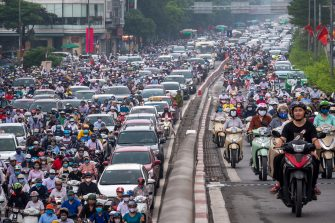 HANOI, VIETNAM - MAY 19: Motorbike riders with face masks are stuck in traffic during the morning peak hour on May 19, 2020 in Hanoi, Vietnam. Though some restrictions remain in place, Vietnam has lifted the ban on certain entertainment facilities and non-essential businesses, including pubs, cinemas and spas & other tourist attractions to recover domestic tourism. On April 23, the Ministry of Transport started to increase domestic flights and trains to major destinations with limited passenger capacity. As of May 19, Vietnam has confirmed 324 cases of coronavirus disease (COVID-19 ) with no deaths in the country, 263 fully recovered and no new case caused by community transmission for 33 days. (Photo by Linh Pham/Getty Images)