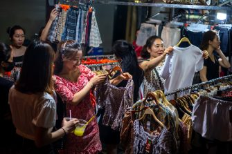 HANOI, VIETNAM - MAY 16: Shoppers look at clothes at the weekend night market in the Old Quarter on May 16, 2020 in Hanoi, Vietnam. Though some restrictions remain in place, Vietnam has lifted the ban on certain entertainment facilities and non-essential businesses, including pubs, cinemas and spas & other tourist attractions to recover domestic tourism. On April 23, the Ministry of Transport started to increase domestic flights and trains to major destinations with limited passenger capacity. As of May 16, Vietnam has confirmed 318 cases of coronavirus disease (COVID-19 ) with no deaths in the country, 260 fully recovered and no new case caused by community transmission for 30 days.