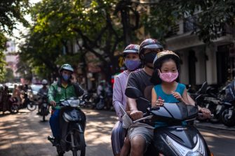 HANOI, VIETNAM - MAY 17: People wear face masks amid concerns of the spread of the Coronavirus (COVID-19) while commuting in the Old Quarter on May 17, 2020 in Hanoi, Vietnam. Though some restrictions remain in place, Vietnam has lifted the ban on certain entertainment facilities and non-essential businesses, including pubs, cinemas and spas & other tourist attractions to recover domestic tourism. On April 23, the Ministry of Transport started to increase domestic flights and trains to major destinations with limited passenger capacity. As of May 17, Vietnam has confirmed 320 cases of coronavirus disease (COVID-19 ) with no deaths in the country, 260 fully recovered and no new case caused by community transmission for 31 days.