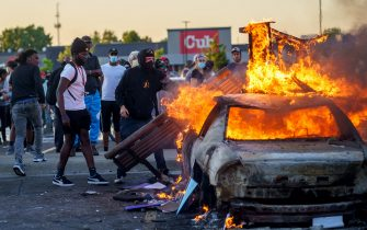 Protesters throw objects onto a burning car outside a Target store near the Third Police Precinct on May 28, 2020 in Minneapolis, Minnesota, during a demonstration over the death of George Floyd, an unarmed black man, who died after a police officer kneeled on his neck for several minutes. - Authorities in Minneapolis and its sister city St. Paul got reinforcements from the National Guard on May 28 as they girded for fresh protests and violence over the shocking police killing of a handcuffed black man. Three days after a policeman was filmed holding his knee to George Floyd's neck for more than five minutes until he went limp, outrage continued to spread over the latest example of police mistreatment of African Americans. (Photo by kerem yucel / AFP) (Photo by KEREM YUCEL/AFP via Getty Images)