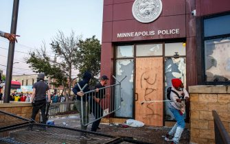 Protesters use a barricade to try and break the windows of the Third Police Precinct on May 28, 2020 in Minneapolis, Minnesota, during a protest over the death of George Floyd, an unarmed black man, who died after a police officer kneeled on his neck for several minutes. - Authorities in Minneapolis and its sister city St. Paul got reinforcements from the National Guard on May 28 as they girded for fresh protests and violence over the shocking police killing of a handcuffed black man. Three days after a policeman was filmed holding his knee to George Floyd's neck for more than five minutes until he went limp, outrage continued to spread over the latest example of police mistreatment of African Americans. (Photo by Kerem Yucel / AFP) (Photo by KEREM YUCEL/AFP via Getty Images)