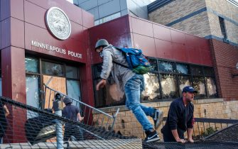 Protesters try to break into the Third Police Precinct on May 28, 2020 in Minneapolis, Minnesota, during a protest over the death of George Floyd, an unarmed black man, who died after a police officer kneeled on his neck for several minutes. - Authorities in Minneapolis and its sister city St. Paul got reinforcements from the National Guard on May 28 as they girded for fresh protests and violence over the shocking police killing of a handcuffed black man. Three days after a policeman was filmed holding his knee to George Floyd's neck for more than five minutes until he went limp, outrage continued to spread over the latest example of police mistreatment of African Americans. (Photo by Kerem Yucel / AFP) (Photo by KEREM YUCEL/AFP via Getty Images)
