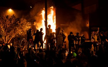 MINNEAPOLIS, MN - MAY 28: Protesters cheer as the Third Police Precinct burns behind them on May 28, 2020 in Minneapolis, Minnesota. As unrest continues after the death of George Floyd, police abandoned the precinct building, allowing protesters to set fire to it. (Photo by Stephen Maturen/Getty Images)
