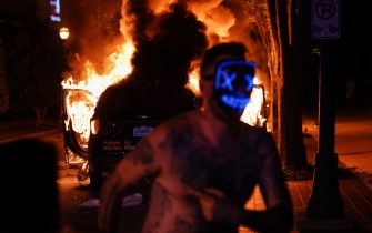 ATLANTA, GA - MAY 29: A man wearing a 'Purge' mask runs in front of a burning police car during a protest on May 29, 2020 in Atlanta, Georgia. Demonstrations are being held across the US after George Floyd died in police custody on May 25th in Minneapolis, Minnesota.   Elijah Nouvelage/Getty Images/AFP == FOR NEWSPAPERS, INTERNET, TELCOS & TELEVISION USE ONLY ==