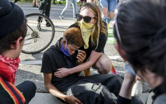 DENVER, CO - MAY 29: A woman comforts a boy who was pepper sprayed during a protest on May 29, 2020 in Denver, Colorado. This was the second day of protests in Denver, with more demonstrations planned for the weekend. Demonstrations are being held across the US after George Floyd died in police custody on May 25th in Minneapolis, Minnesota.  Michael Ciaglo/Getty Images/AFP == FOR NEWSPAPERS, INTERNET, TELCOS & TELEVISION USE ONLY ==