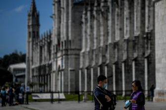 Tourists wearing protective face masks stand outside the Jeronimos Monastery in Lisbon on March 12, 2020. - The coronavirus global outbreak has left virtually no economic sector untouched, though travel and tourism have been particularly hard-hit as countries institute travel bans and quarantine requirements. Portugal has detected 78 confirmed cases so far, according to official numbers released on March 12. (Photo by PATRICIA DE MELO MOREIRA / AFP) (Photo by PATRICIA DE MELO MOREIRA/AFP via Getty Images)