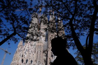 A woman walks in front of the Sagrada Familia in Barcelona on April 10, 2020, during a national lockdown to prevent the spread of the COVID-19 disease. - Spain has recorded its lowest daily death toll from the new coronavirus in 17 days, with 605 people dying, the government said. (Photo by Pau Barrena / AFP) (Photo by PAU BARRENA/AFP via Getty Images)