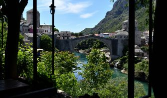 """TOPSHOT - The deserted """"Old Bridge"""" of Mostar, usually riddled with groups of tourists is seen from an empty restaurant terrace, on May 8, 2020. - With more than 90 percent of those tourists foreigners, the town is now facing a particularly painful collapse as the COVID-19 pandemic caused by the novel coronavirus, shutters international borders and severely curbs air travel, sending the global tourism industry into a tailspin. (Photo by ELVIS BARUKCIC / AFP) (Photo by ELVIS BARUKCIC/AFP via Getty Images)"""