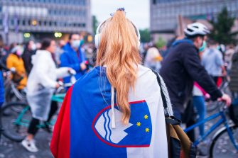 A woman wears a Slovenian flag as protesters, some wearing face masks, stand with their bicycles outside the Slovenian National Assembly building and block the centre the capital Ljubljana, on May 15, 2020, during a demonstration to protest against the centre-right government, accusing it of corruption and of using the COVID-19 (the novel coronavirus) crisis to restrict freedom. (Photo by Jure Makovec / AFP) (Photo by JURE MAKOVEC/AFP via Getty Images)