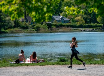 A woman jogs past sunbathers next to a canal at Djurgarden in Stockholm, on May 26, 2020, as temperatures reached 20 degrees Celsius. (Photo by Anders WIKLUND / TT News Agency / AFP) / Sweden OUT (Photo by ANDERS WIKLUND/TT News Agency/AFP via Getty Images)