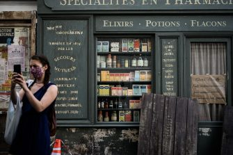 TOPSHOT - A woman takes a picture in front of a cinema set as work resume prior to filming in a street of the Montmartre hill touristic neighbourhood of Paris on May 26, 2020 after the filming was halted amid the crisis caused by the Covid-19 pandemic (novel coronavirus) (Photo by Philippe Lopez / AFP) (Photo by PHILIPPE LOPEZ/AFP via Getty Images)