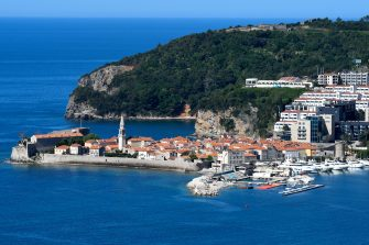"""This picture taken on May 13, 2020, shows a general view of the town of Budva, on the Adriatic coast of Montenegro. - Less than two months after detecting its first infection, Montenegro is the first country in Europe to declare itself coronavirus-free, a success story the tiny country hopes will lure tourists to its dazzling Adriatic coast this summer. Tourism operators have already seized the opportunity to brand Montenegro as """"Europe's First COVID-19 Free Country"""" in videos promoting its stunning natural beauty, with beaches snaking along the south and rugged mountains in the north. (Photo by SAVO PRELEVIC / AFP) (Photo by SAVO PRELEVIC/AFP via Getty Images)"""