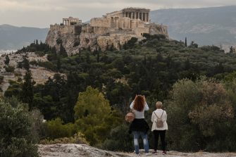 People visit the Pnyx Hill in Athens overlooking the ancient Acropolis on May 29, 2020 as Greece eases lockdown measures taken to curb the spread of the COVID-19 (the novel coronavirus). - Greece announced a list of 29 countries deemed to fit the epidemiological profile , allowed to fly to Greece from 15 June as the country opens for tourists. (Photo by Louisa GOULIAMAKI / AFP) (Photo by LOUISA GOULIAMAKI/AFP via Getty Images)